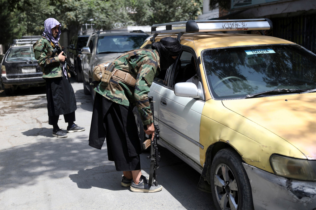 Taliban fighters search a vehicle at a checkpoint on the road in the Wazir Akbar Khan neighborhood in the city of Kabul, Afghanistan.