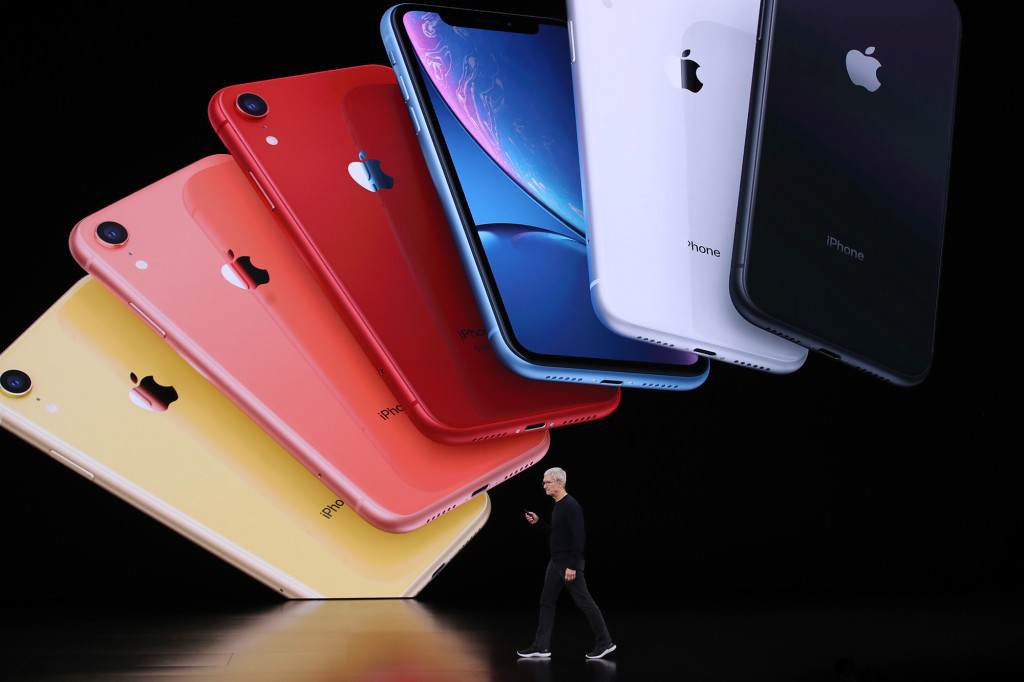 Tim Cook walking onstage with images of iPhones in different colors seen onscreen in the background